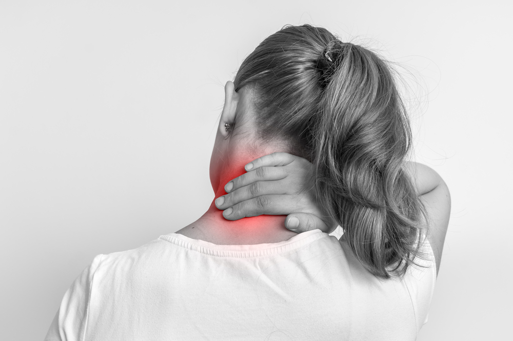woman with neck pain holding the back of her neck